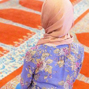 Woman wearing an orange hijab kneeling in a mosque