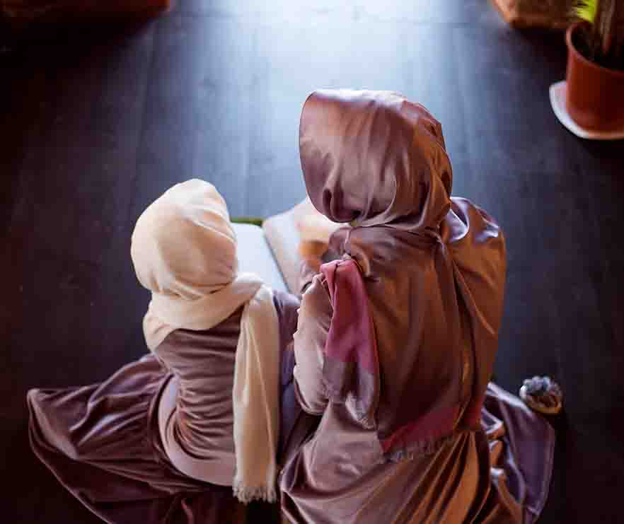 A mother and daughter reading the Quran