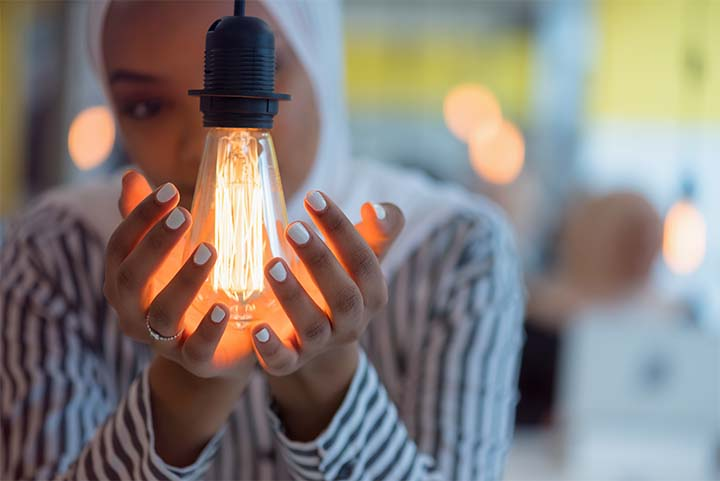 A woman wearing a white hijab cradles a lit light bulb in her hands