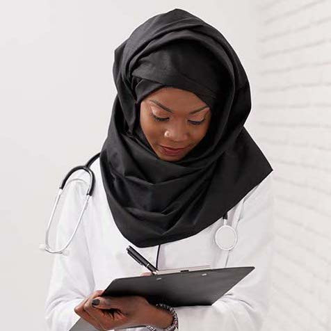 A doctor wearing a black hijab checks a patient chart on a clipboard