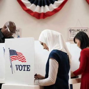 A woman wearing a white hijab at the voting booth