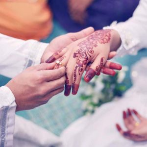 Wedding Couple Putting A Gold Ring On Hand