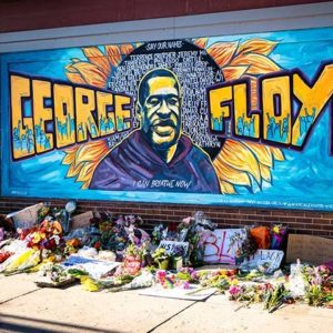 """A brick wall mural with """"George Floyd"""" in large block letters and an image of George Floyd. Flowers, notes, and posters were placed on the sidewalk below."""