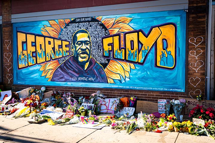 "A brick wall mural with ""George Floyd"" in large block letters and an image of George Floyd. Flowers, notes, and posters were placed on the sidewalk below."