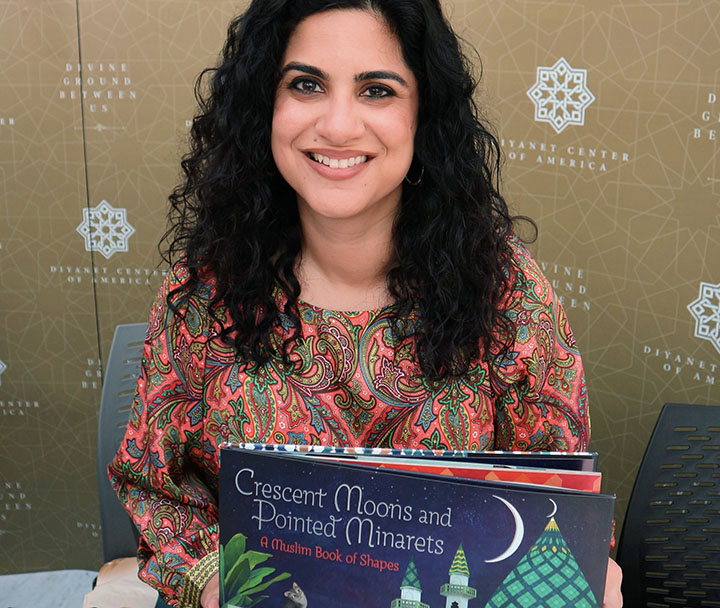 "Author Hena Khan holding her children's book, ""Crescent Moons and Pointed Minarets"""
