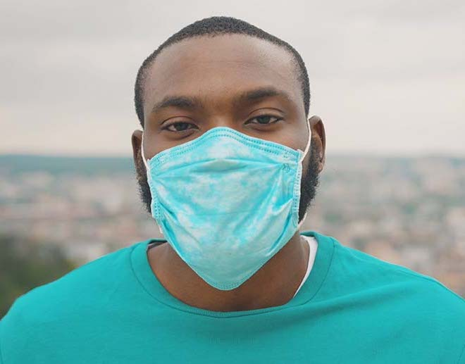 Portrait of man wearing protective face mask looking straight standing on the hilltop above city