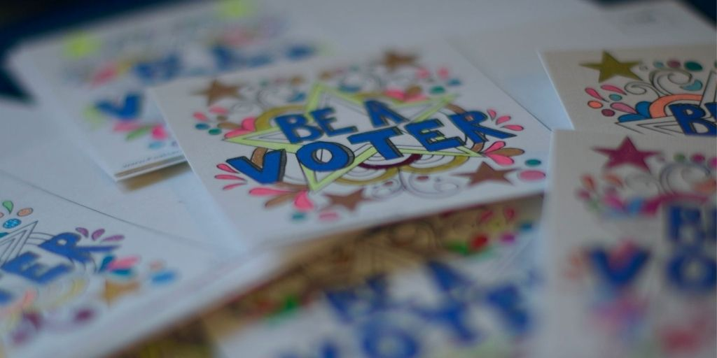 "A notecard that reads ""Be a voter"""