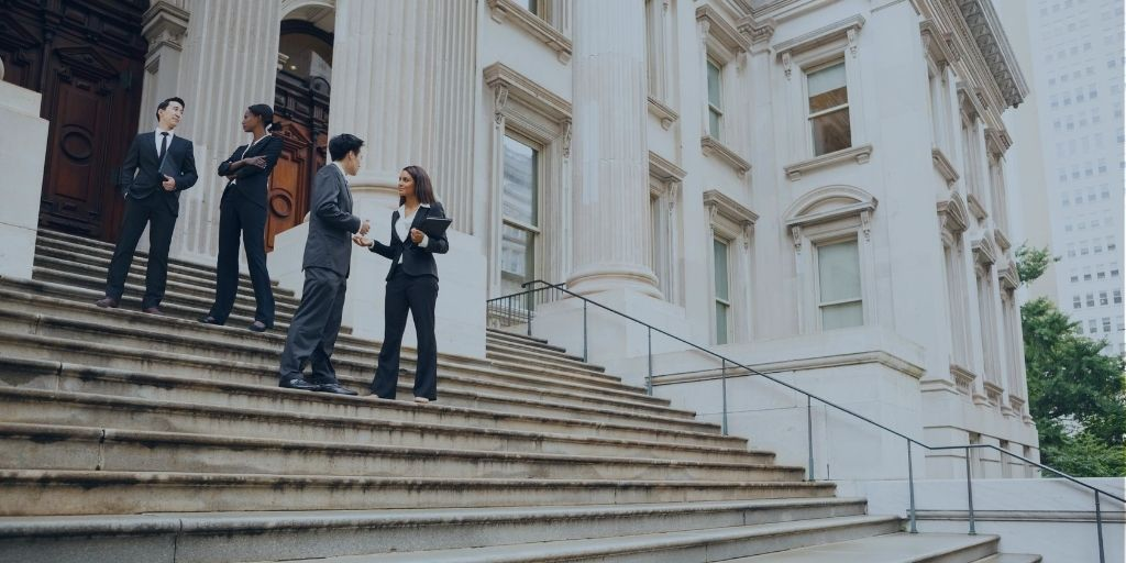 Four well dressed professionals in discussion on the exterior steps of a government building