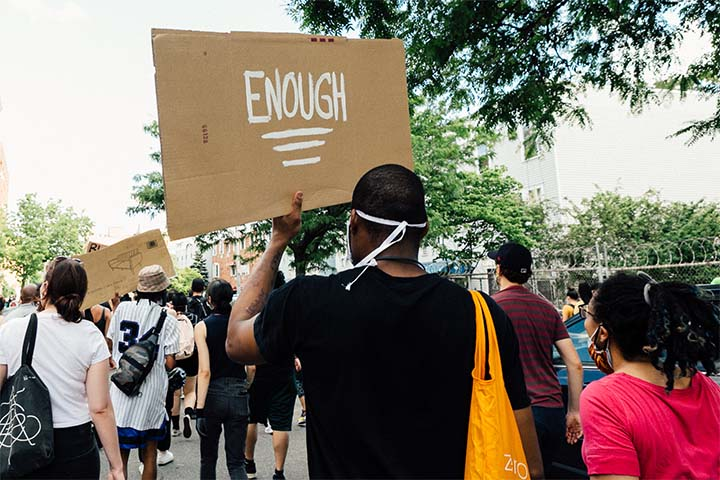 "The back of a masked Black Lives Matter protester holding up a cardboard sign that reads ""ENOUGH"""