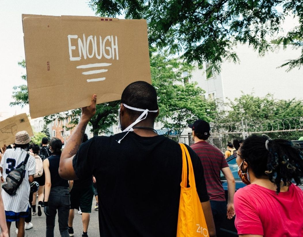 """The back of a masked Black Lives Matter protester holding up a cardboard sign that reads """"ENOUGH"""""""